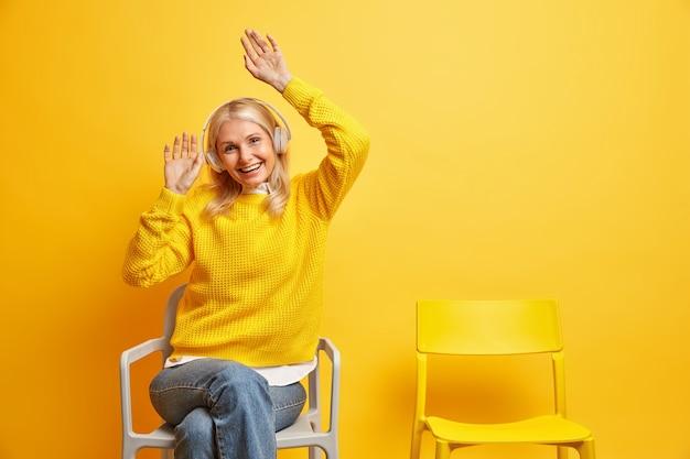 Mensen vrijetijdsbesteding en entertainment concept. geamuseerde blonde oude vrouw heft armen zit op een comfortabele stoel en luistert naar audiotrack via draadloze koptelefoons