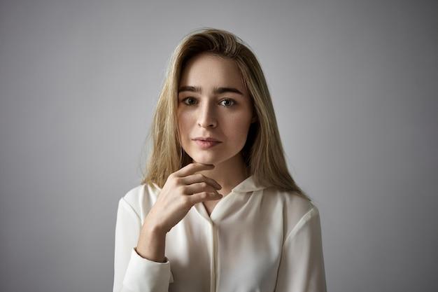 Mensen, vrouwelijkheid, schoonheid, stijl en mode-concept. horizontale opname van aantrekkelijke blonde jonge blanke vrouw met losse haren en sproeten die haar kin raken, met een serieuze, doordachte blik
