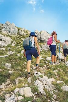 Mensen wandelen in de bergen met stokken