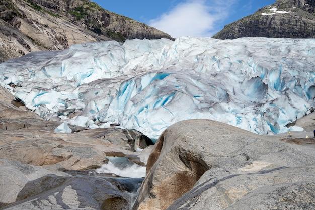 Mensen wandelen naar blauwe gletsjer in de bergen