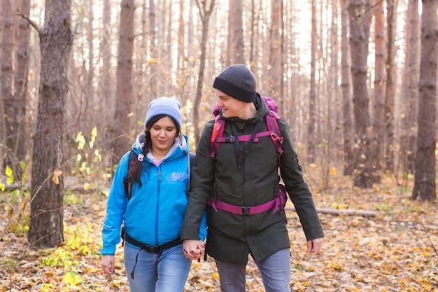 Mensen wandelen toerisme en natuur concept paar toerist wandelen in herfst bos