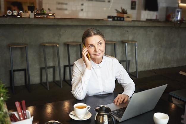 Mensen, werk, moderne levensstijl, technologie en communicatieconcept. foto van aantrekkelijke zelfverzekerde rijpe zakenvrouw in formele slijtage met telefoontje durign koffiepauze in café en met behulp van laptop