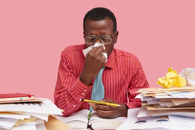 Mensen, werk, ziekteconcept. allergische donkere man gebruikt weefsel, heeft loopneus, werkt ziek, bestudeert documentatie