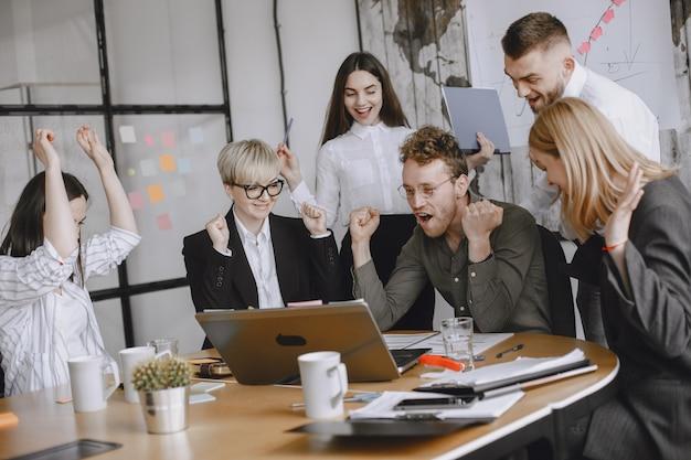 Mensen werken aan het project. mannen en vrouwen in pakken aan tafel zitten. zakenlieden gebruiken een laptop.