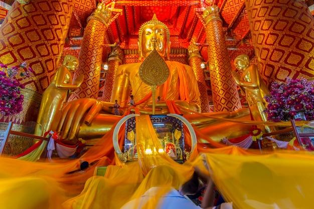 Mensen werken met doek op boeddha-afbeelding in wat phanan choeng-tempel