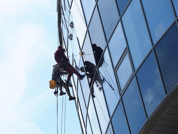 Mensen werken professioneel op hoogte ramen wassen