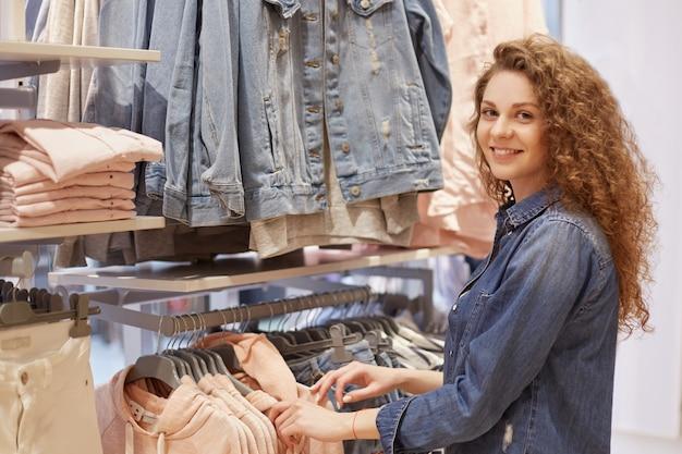 Mensen, winkelen, stijl, mode en verkoop concept. gelukkig mooie jonge vrouw met krullend haar, gekleed in denim jasje