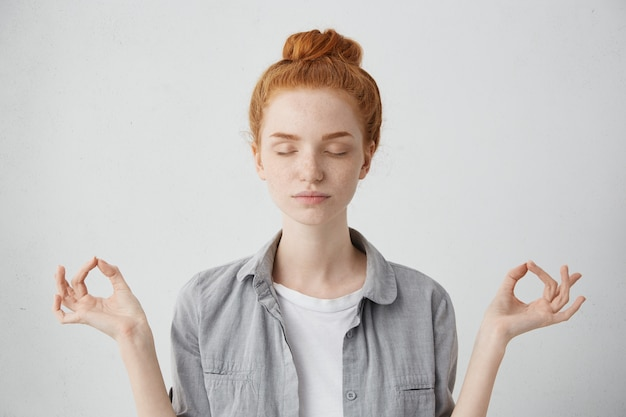 Mensen, yoga en een gezonde levensstijl. portret van prachtige jonge roodharige vrouw die de ogen gesloten houdt terwijl ze binnenshuis mediteert, gemoedsrust oefent, vingers in mudra-gebaar houdt