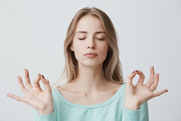 Mensen, yoga en een gezonde levensstijl. prachtige jonge blonde vrouw gekleed in lichtblauwe trui ogen gesloten houden terwijl mediteren binnenshuis, gemoedsrust oefenen, vingers houden in mudra gebaar