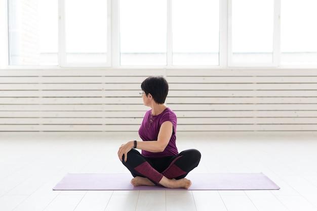 Mensen, yoga, sport en gezondheidszorgconcept - aantrekkelijke vrouw van middelbare leeftijd die zich uitrekt en binnen zit