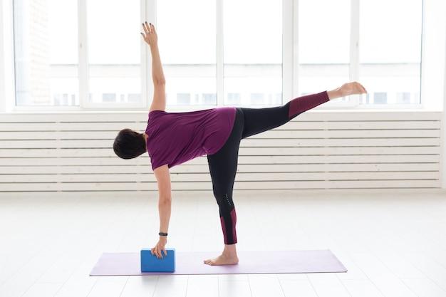 Mensen, yoga, sport en gezondheidszorgconcept. vrouw die op middelbare leeftijd yoga beoefent