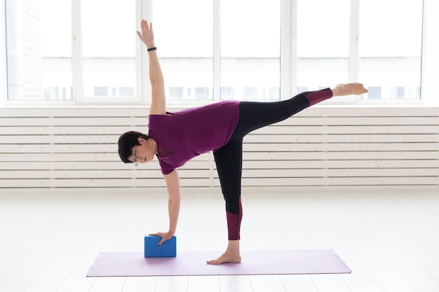 Mensen, yoga, sport en gezondheidszorgconcept - vrouw die van middelbare leeftijd yoga beoefent, met behulp van stretching