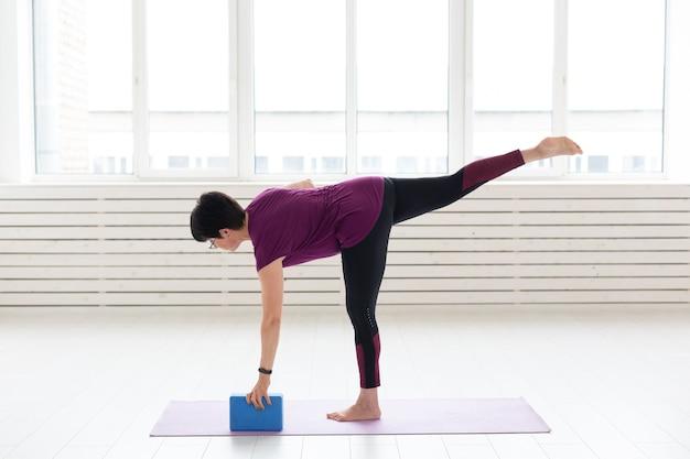 Mensen, yoga, sport en gezondheidszorgconcept. vrouw van middelbare leeftijd beoefenen van yoga, met behulp van uitrekkende kubus