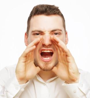 Mensen, zaken en lifestyle concept - knappe zakenman in wit overhemd schreeuwen tijdens het kijken naar camera en staande tegen witte ruimte