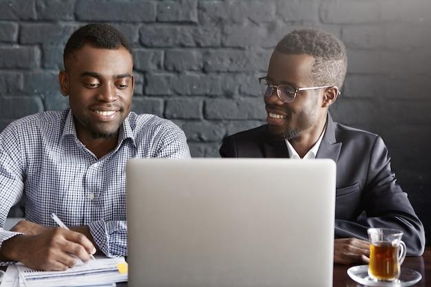 Mensen, zaken, teamwork en samenwerking concept. twee afro-amerikaanse werknemers in formele kleding samen te werken aan gemeenschappelijke presentatie op generieke laptopcomputer in moderne kantoor