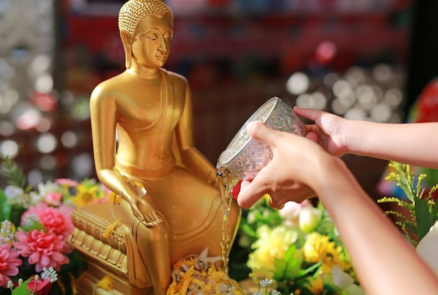 Mensen zegenen heilig water en betalen respect voor het boeddhabeeld.