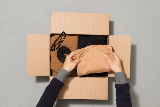 Mensen zetten kleren in een donatiebox