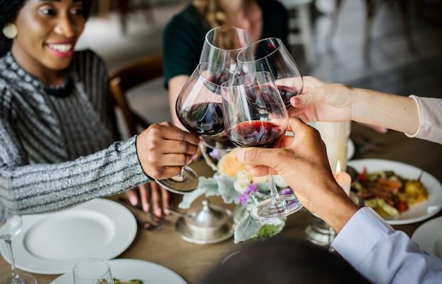 Mensen zich vastklampende wijnglazen samen in restaurant