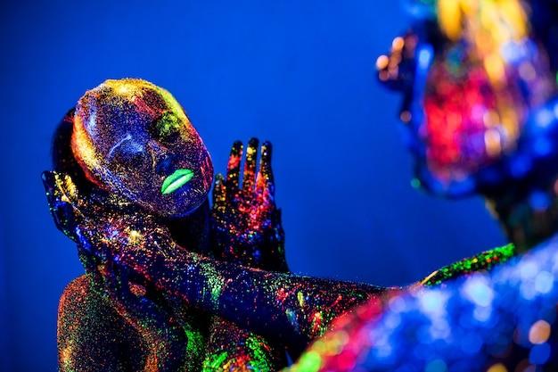 Mensen zijn gekleurd fluorescerend poeder. een paar liefhebbers dansen in een disco.