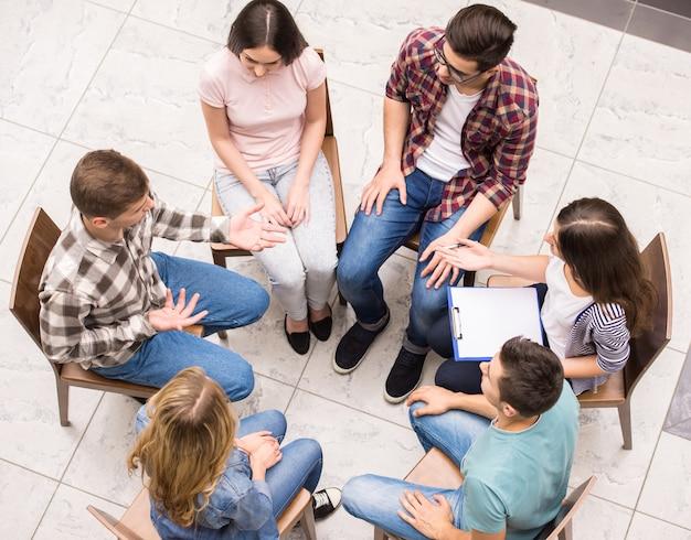 Mensen zitten dicht bij elkaar en communiceren.