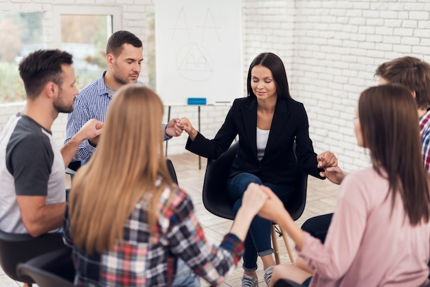 Mensen zitten en hand in hand tijdens therapiesessie.