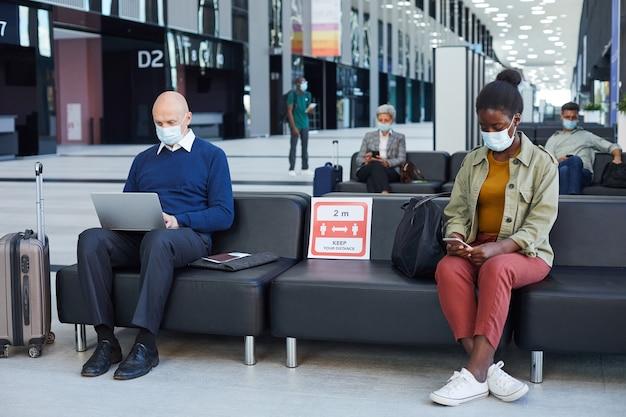 Mensen zitten in de wachtkamer en gebruiken gadgets op de luchthaven