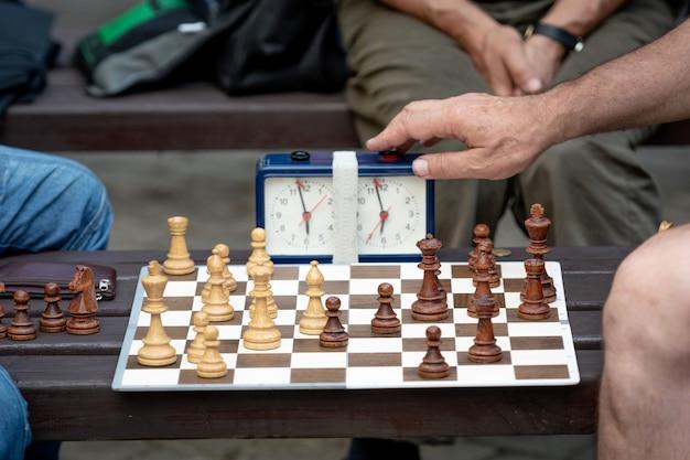 Mensen zitten in het park op banken en schaken.