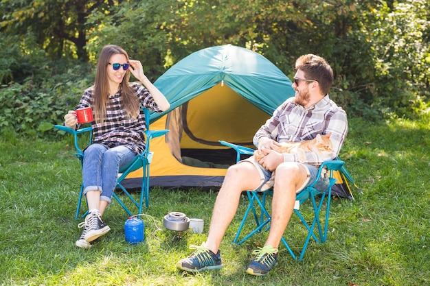 Mensen, zomertoerisme en natuur concept - jong koppel zit in de buurt van een tent.
