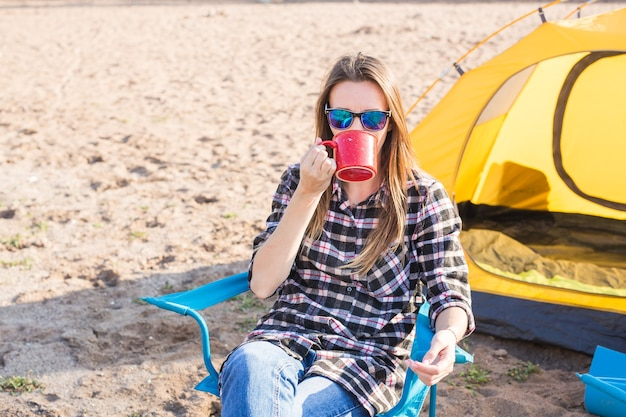 Mensen, zomertoerisme en natuurconcept - jonge vrouw die in de buurt van tent zit