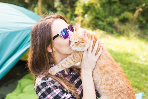 Mensen, zomertoerisme en natuurconcept - jonge vrouw met kat in de buurt van tent.