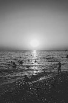 Mensen zwemmen in de zee in de avond bij zonsondergang, zwart-wit foto
