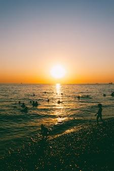 Mensen zwemmen 's avonds bij zonsondergang in de zee