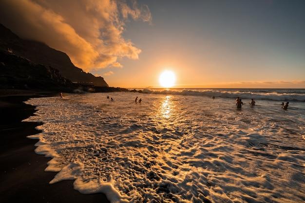 Mensen zwemmen 's avonds in de oceaan en bewonderen de prachtige zonsondergang op het eiland tenerife.spain