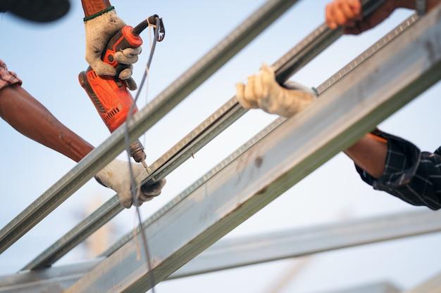 Mensenarbeider gebruikt een boormachine om een metalen dakwerkbaan met schroeven te bevestigen.