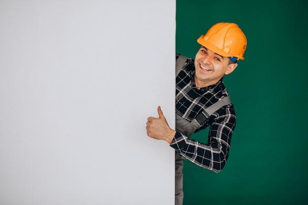 Mensenarbeider in bouwvakker op groene muur wordt geïsoleerd die