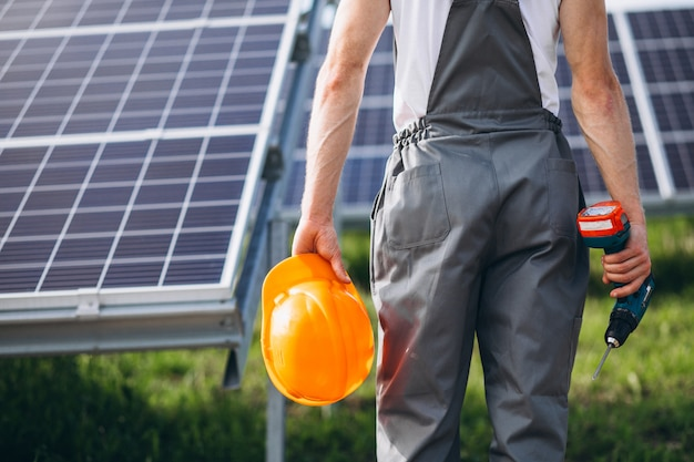 Mensenarbeider in firld door de zonnepanelen