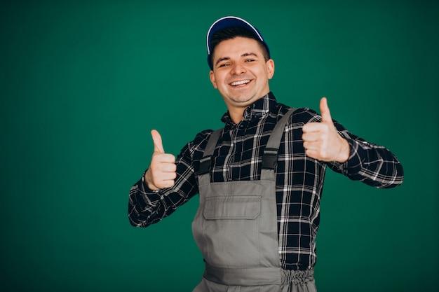 Mensenarbeider in hoed op groene muur wordt geïsoleerd die