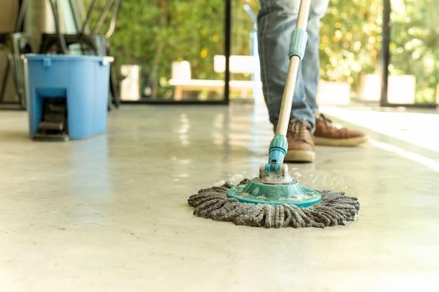 Mensenarbeider met zwabber en emmer schoonmakende vloer in het koffie.