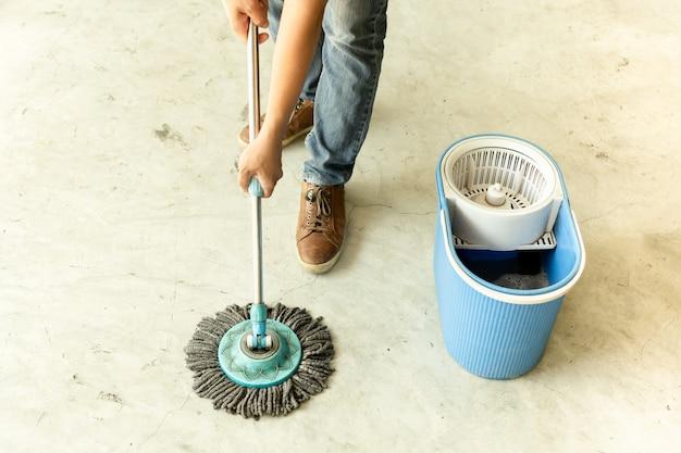 Mensenarbeider met zwabber schoonmakende vloer in het koffie.