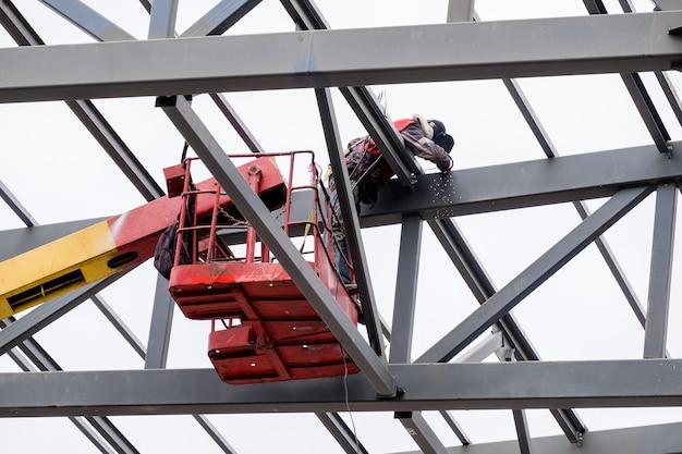 Mensenarbeider op een kraan voert hoogbouwwerkzaamheden uit aan het lassen van metalen constructies van een nieuwe toren op hoogte.