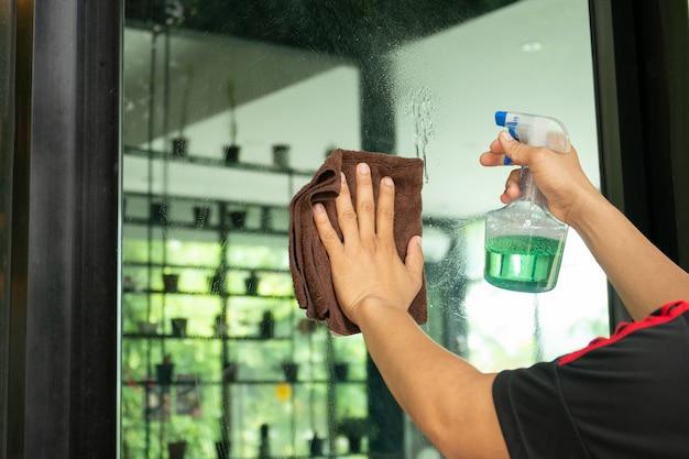 Mensenarbeider schoonmakende vensters met doek en nevelfles bij koffiewinkel.