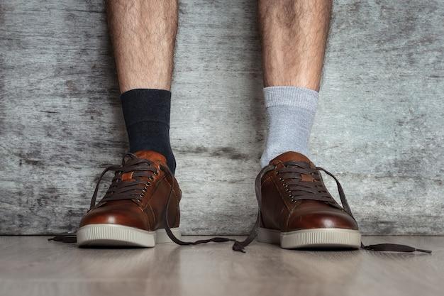 Mensenbenen in bruine leerschoenen en verschillende sokken op een donkere achtergrond