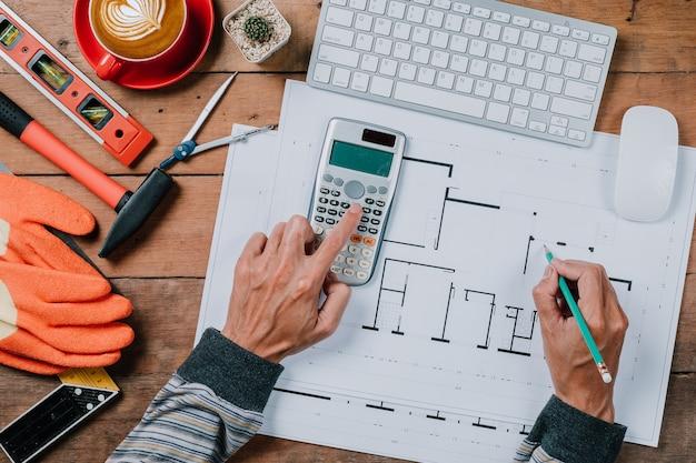 Mensenconcept architectenhanden die met calculator en pen aan huis blauwe druk werken.