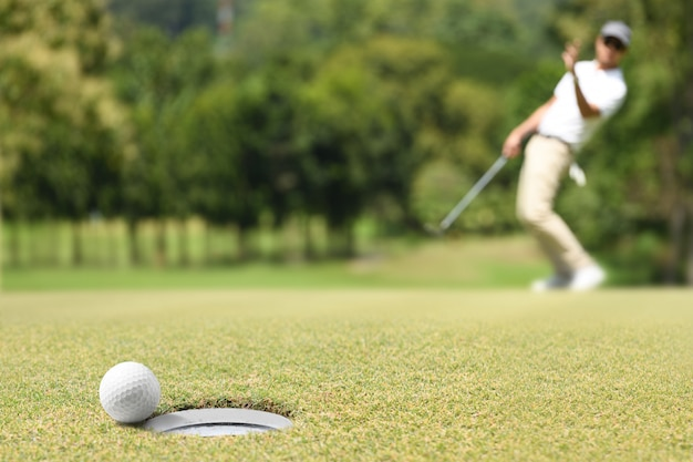 Mensengolfspeler die na een golfbal op een groen golf toejuichen