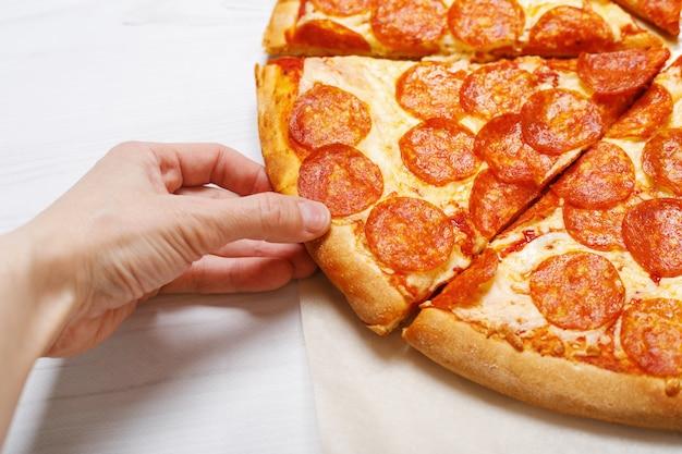 Mensenhand die een plak van pizza houdt.