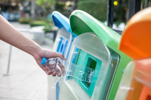 Mensenhand die en plastic flessenafval houden in vuilnisafval houden.