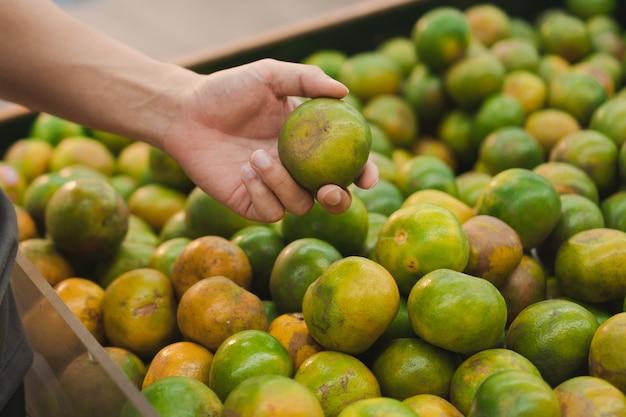 Mensenhand die en verse sinaasappelen kopen opheffen bij kruidenierswinkelopslag of supermarkt.