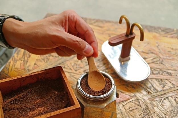 Mensenhand die grondkoffie voor het brouwen van aromatische espresso voorbereiden