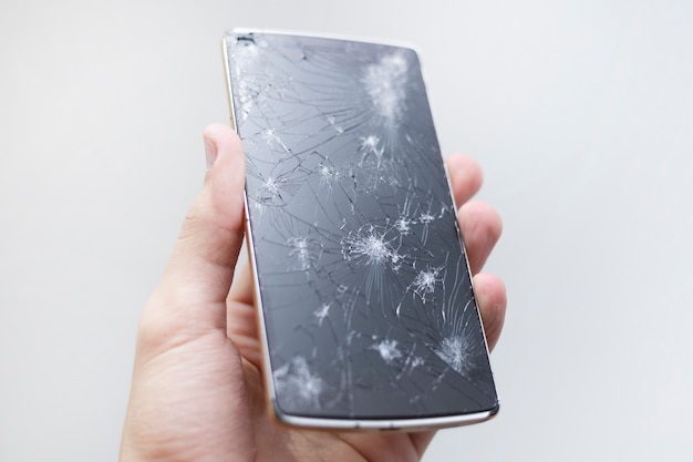 Mensenhand die mobiele telefoon met het gebroken scherm houden