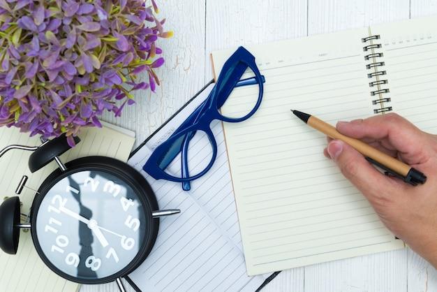 Mensenhand die op blanco pagina van notitieboekjedocument schrijven met pen